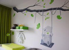 Muurschildering van een Me to You beer op een schommel aan een boomtak in een babykamer.    Mural wall painting baby nursery bear