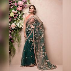 Finely Edged in a Zardosi border, this Deep Green Tulle Saree is Hand Embroidered with Pastel Florals in Leafy Foliage . . .…