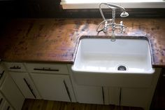 Copper countertop, farmhouse sink.  Beautiful faucet.  How would this look with pine cabinets and unlacquered brass for the faucet?  Stunning I think.