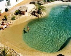 A backyard pool that looks like a beach. This would be so relaxing why would you ever want to leave your own backyard? This pool looks like it could be kid and animal friendly.