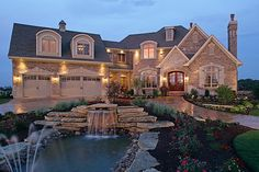 I love the natural stone, I love the water feature, I LOVE the angles of the house, not to mention the chimney and double front doors!