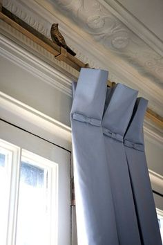 Window Fashion: Silk panels with inverted box pleats are hung from gold square rods accented by birds perched across the rod. Pretty bows finish the heading and hide the stitching.