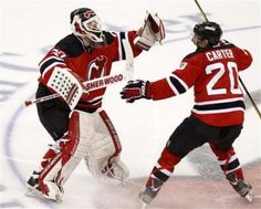 Martin Brodeur and Ryan Carter celebrate at center ice.