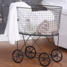 Vintage chic laundry basket stylishly stores magazines, games, bath towels, or even dirty laundry! Features a distressed black metal finish and vintage style carriage wheels.