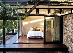 Master bedroom with sliding glass doors as walls that lead to a wraparound porch. (By GASS Architecture Studios in Johannesburg, South Africa.)