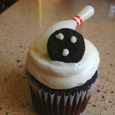 Bowling inspired cupcake. Great for kids bowling party. Just add three dots of icing or melted white chocolate to a mini Oreo to create a bowling ball. Pin is from a party favor toy set.