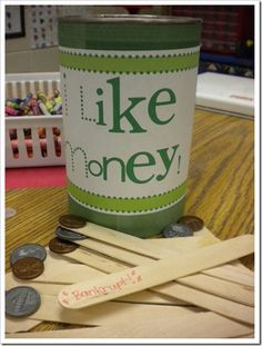 "It's super easy to make too! Just some popsicle sticks and plastic coins.  You can use stickers too – I like the coins because the kids can feel the edges.  I used a large ""nut"" container, and the popsicle sticks fit PERFECTLY inside – you can even put the lid on for storage!  Hot glue (or super glue!) the coins on to the sticks.  On a couple of the sticks write ""Bankrupt. ""  Kids sit in a circle and pass the can around – when it is their turn, the child takes one and says the name of the co..."