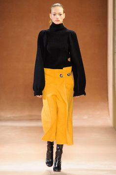 The key cut for pants is decidedly breezy and above the ankle. Culottes make it that much easier to show off a great pair of boots, and Fall's variety come with pleats, finished in leather, or washed in high-octane hues. Victoria Beckham Fall 2015