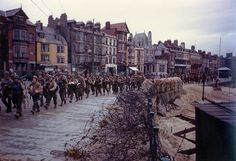 U.S. Soldiers march through Weymouth, Dorset, en route to board landing ships for the invasion of France, circa late May or early June 1944.