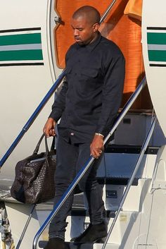 Kanye West wearing  Dickies Long Sleeve Work Shirt, Acne Ace Used Cash Jeans, Bottega Veneta Ebano Intrecciato VN Large Duffel, Rolex Day-Date II President 41mm Watch