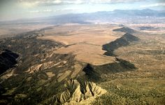 111-32: Lava-capped mesa by Rio Grande southwest of Taos, NM. View to the southwest toward Jemez Mountains in background. Note the difference in slope wasting between the south-facing and north-facing slopes (11Apr66)