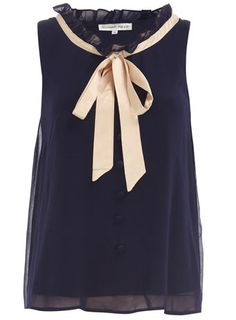 Fashion: New York City Style. At The Office. A sleeveless navy top with a bow and a frilly collar.