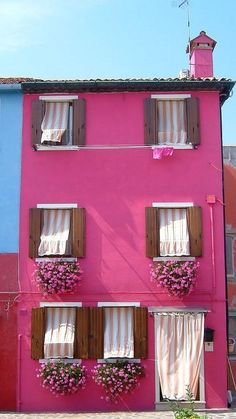Oh my gosh, I think I know where this is because I've been there! This has to be the Burano Island, in Venice, Italy. All the houses in the village are painted in these beautiful, bright colors. It is lovely!!