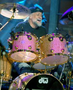"""Mick Fleetwood on pink quilt DW drumkit. RESEARCH #DdO:) - https://www.pinterest.com/DianaDeeOsborne/drums-drumming-joy/ - DRUMS & DRUMMING JOY: Few think of Michael John Kells """"Mick"""" Fleetwood as a British actor. This musician is best known as drummer and co-founder of most successful bands of all time, 1967 new rock group Fleetwood Mac, for over four decades. Photo pinned via drumhead 843."""