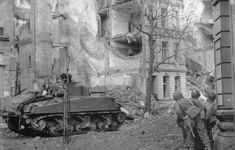 Soldiers of the 104th Infantry Division guarding the walls of the post office in Cologne, while a M4 Sherman opens the way to the center of the city.