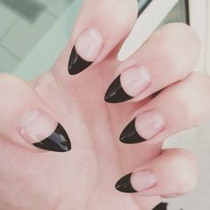 Negative space black tipped stiletto nails.