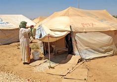 Syrian refugee woman hangs laundry in front of her tent in Zaatari camp in Jordan (August 2012)