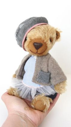 Nora is 22cm bear made of special material for bears - mohair, has got 5 joints (double for the head), glass eyes, stuffed with fibrefill and steel pallets, shaded with oil paint, designed to sit. She wears a cotton trousers and dress, a sweater made of wool and a beret.