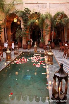 Marrakech pool adorned with customary wedding decor of brass lanterns, luminous candles, and floating flower petals [photo by Virginie Faucher, Paris, France].... #MoroccanDecor