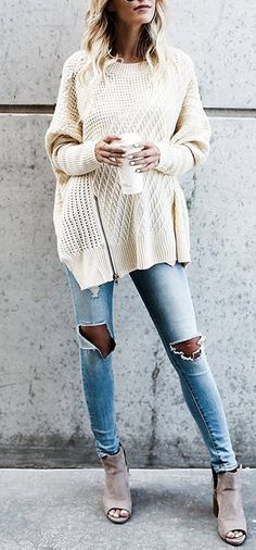 a chunky cable knit sweater with zipper on the bottom paired with ripped jeans
