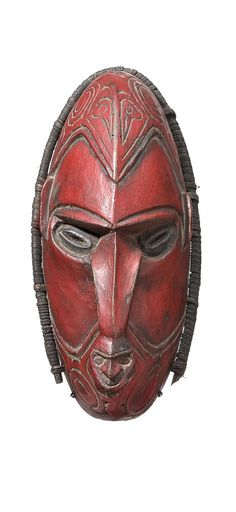 SMALL HUNTING CHARM MASK (GAMEI PEOPLE, LOWER RAMU RIVER, MADANG PROVINCE, PAPUA NEW GUINEA)  mid 20th Century  25.0 cm height  unusual example with a second tiny mask on the end of the elongated nose, painted with red 'trade paint', pierced around the edges with woven split cane surround, avian design incised carving on the forehead, carried in a small string bag for protection and to bring good hunting