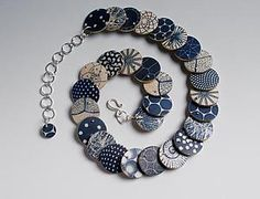 Water based black and indigo image transfer on pearlized ivory-colored polymer clay beads, connected with fine silver ball head pins and sterling silver heishi beads. Hand forged sterling clasp and adjustable chain. Chain end finished with smaller bead. Reverse side is black with silver components. Each piece is unique. Patterning may vary slightly from that shown