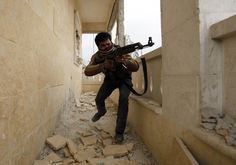 A Free Syrian Army fighter aims his weapon as he takes up a position in Aleppo's Sheikh Saeed neighborhood. Photographer Molhem Barakat.Chilling Pictures Taken By The Teenage Photographer Who Was Killed In Syria