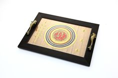 This stunning tray with handles in the shape of dolphin and hand painting done on Silk. Crafted out of recycled wood along with brass dhokra figures at the center. The borders are made up of Acrylic. Top of the tray is covered with plastic.