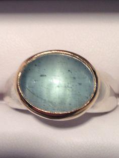 Zilveren ring, aquamarijn in gouden zetkast