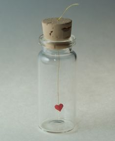 get a selection of little vials from Michaels, cut two hearts from red construction paper (tiny!), glue them to red thread, then used a needle to pull the thread through the cork. I cut the thread off flush with the cork and smeared a dap of glue on it. SO CUTE! heart message in a bottle-
