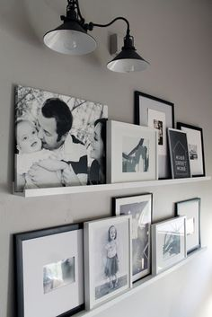Such a cute gallery wall alternative. Like how they worked with the sconce too. | Chris Loves Julia: Photo Ledges O Fun Picture Ledge Bedroom, Ikea Picture Shelves, Gallery Wall Shelves, Photo Shelf, Living Room Picture Ideas, Photo Gallery Walls, Diy Picture Rail, Dining Room Picture Wall, Picture Rail Hanging