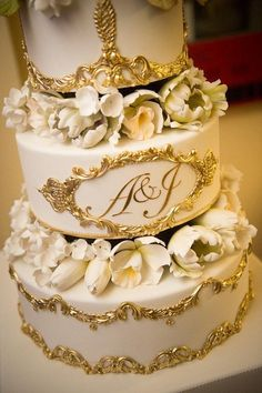 Gorgeous gold and white wedding cake with initials.