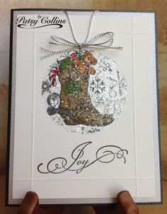 """By Patsy Collins. Score near edges of white cardstock panel. Lay a negative circle mask on panel. Stamp """"Christmas Boot"""" (Texana Designs Stamps) in black. Stamp again on Post-it Note; hand cut; place over image on cardstock. Stamp snowflakes after stamping off. Remove boot mask. Color boot with Memento markers. Apply glue sparingly within circle; spread with foam brush. Cover with coarse glitter. Remove mask. Add sentiment. Layer on silver mat. Add cord and bow. Pop up piece on black card…"""