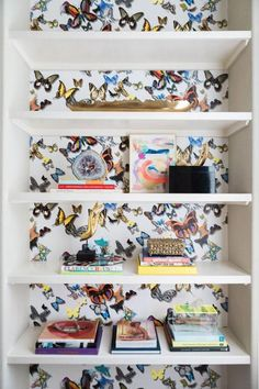Add some color and fun to your wall by adding an accent wallpaper to the wall of your shelves.