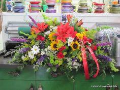 Casket spray with orange lilies, sunflowers, blue delphinium, green button mums, white daisies. Casket Flowers, Funeral Flowers, Funeral Sprays, Casket Sprays, Blue Delphinium, Sympathy Flowers, Green Button, Lilies, Sunflowers
