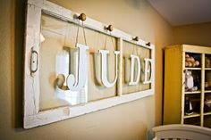 I think this may be the best idea I've seen lately! This was made with an old window pane, some knobs, wooden letters, and craft paper from Hobby Lobby