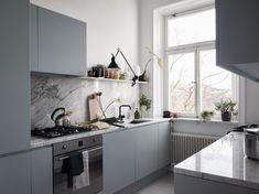Jonas Wagells lägenhet. Inredningsinspiration på Södermalm. Parallellkök med grågröna matta skåpsluckor och carraramarmorskivor.
