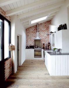 cocina rústica, pared ladrillo visto, muebles madera reciclada pintados blanco, suelo de parquet
