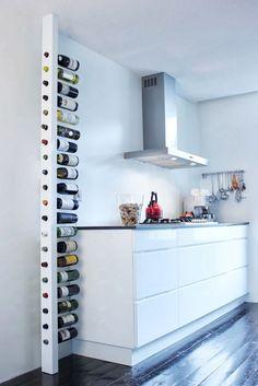 Um pilar que é uma garrafeira vertical, com as garrafas bem à vista e suspensas horizontalmente pelo gargalo. É um design  da empresa hol...