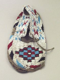 Sioux, Native American. Moccasin with red, white, blue and black geometric beadwork, 1901-1966. Beads, cotton thread, hide, 7 3/4 x 3 1/2 x 3/4 in. or (19.0 cm). Brooklyn Museum, Gift of Mr. & Mrs. Jerome Blum, 66.86.24. Creative Commons-BY (Photo: Brooklyn Museum, CUR.66.86.24_view1.jpg)