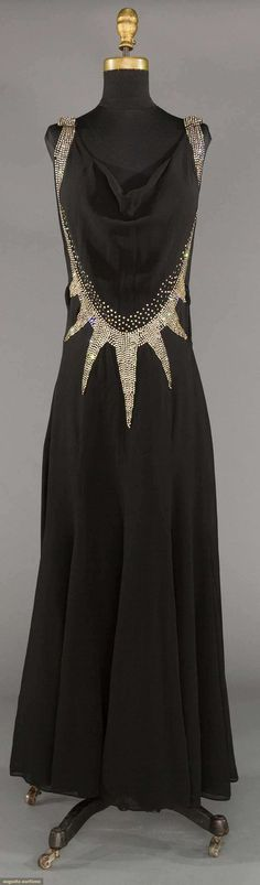 "RHINESTONE DECO EVENING DRESS, 1930s - Lot: 227 May 9, 2017 - CATALOG SALE Sturbridge, Massachusetts - Black silk chiffon w/ wide Deco pattern rhinestone bands, gored skirt, B to 34"", W to 28"", H 36"", (no side opening, couple very small holes to side, large tuck taken in from W to hem seam, 1 tear to chiffon at edge of 1 rhinestone point) fair."