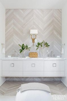 Gray and white herringbone chevron pattern marble backsplash wall in bathroom with double satin finish sinks, dual-lamp shade brass wall sconce, and floating light gray credenza underneath. Love this modern meets traditional mix of interior design ideas!