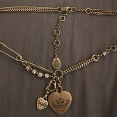 Gold Juicy Couture Heart Charm Necklace Gold Juicy Couture with signature safety pin. Charms featured are gold heart, rhinestone heart, and heart cutout. All rhinestones present.  Slight wear on large heart. Worn twice. Juicy Couture Jewelry Necklaces