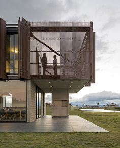 An austere concrete wall screens the transparent lower floor of this house in southern Brazil.