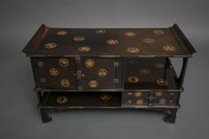 Black Lacquer Tana (tiered tea cabinet) with Gold Crest Design Early 19th century, Japan
