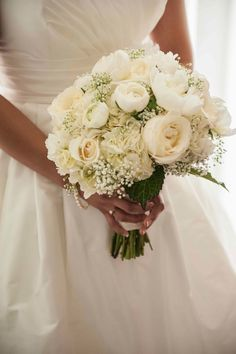 An all white bridal bouquet featuring babies breath, peony, ranunculus, hydrangea and garden rose