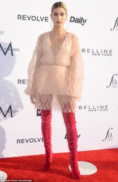 Reaching high: Hailey Baldwinwore kinky red thigh high boots and a flouncy and very plunging dress to the Fashion Los Angeles Awards on Sunday