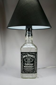 """Looking for ways to repurpose those empty liquor bottles you have hanging around? These Jack Daniel's DIY projects are for you. In college, a group of my friends decorated the """"dining room-kitchen-foyer"""" area of theirdorm with 15 vodka bottles (1.75"""