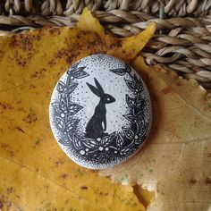 a hand-drawn design, a black rabbit, on a small white stone from a beach in the south of england. it is approximately across its length and White Stone, Hare, Rabbits, Hand Drawn, I Shop, How To Draw Hands, England, Beach, Design