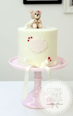 Cute girl's baby shower christening cake in pink and ivory with fondant gumpaste teddy bear cake topper